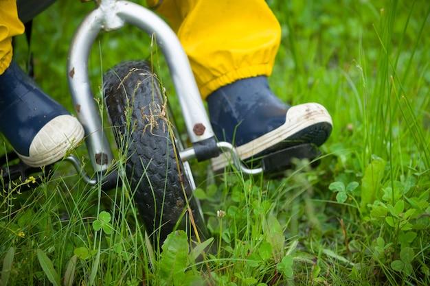 Nahaufnahme von kleinkindkinderfüßen in gummistiefeln und hosen, die nach rai . fahrrad auf grünem gras fahren