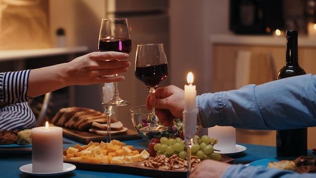 Nahaufnahme von klirrenden rotweingläsern beim romantischen abendessen. fröhliches, fröhliches junges paar, das zusammen in der gemütlichen küche diniert, das essen genießt und romantischen toast zum jubiläum feiert