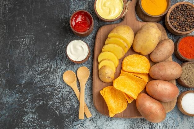 Nahaufnahme von knusprigen pommes und ungekochten kartoffeln auf holzschneidebrett und verschiedenen gewürzen auf grauem tisch