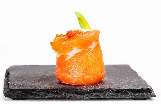 Nahaufnahme von köstlichem gunkan-sushi mit lachs auf weißem hintergrund