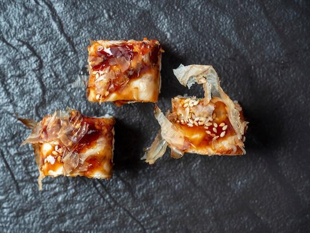 Nahaufnahme von köstlichen brötchen auf strukturierten schwarzen gerichten. ansicht von oben, flach. japanische küche