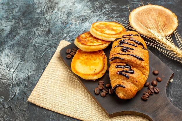 Nahaufnahme von köstlichen croissant-pfannkuchen für die lieben auf der linken seite auf dunkler oberfläche