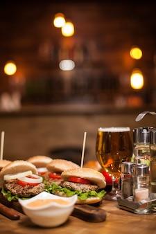 Nahaufnahme von köstlichen frischen hausgemachten burgern mit salat, käse und tomaten mit weißer sauce auf einem schneidebrett. leckere burger.