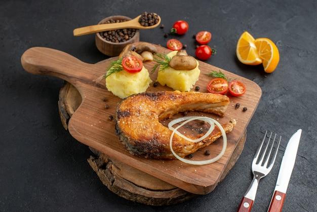 Nahaufnahme von köstlichen gebratenen fischen und pilzen, tomatengrüns auf schneidebrettbesteck, pfeffer auf schwarzer oberfläche