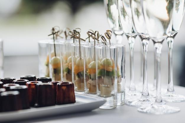 Nahaufnahme von köstlichen gesunden vorspeisen, die auf der geburtstagsfeier serviert werden. selektiver fokus von süßen bananen, kiwi und orangen in gläsern. konzept von catering, desserts, arrangement und dekoration.