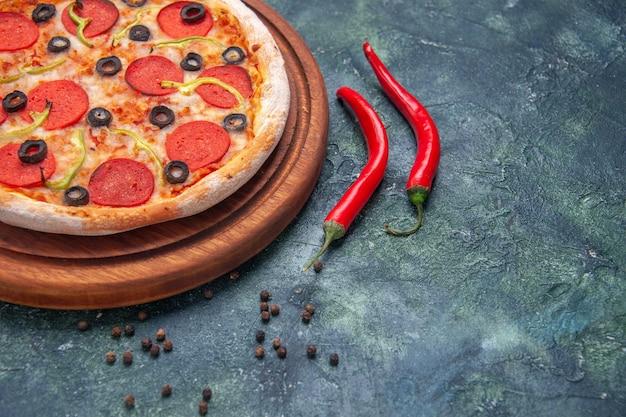 Nahaufnahme von köstlicher pizza auf holzbrett und paprika auf isolierter dunkler oberfläche mit freiem platz