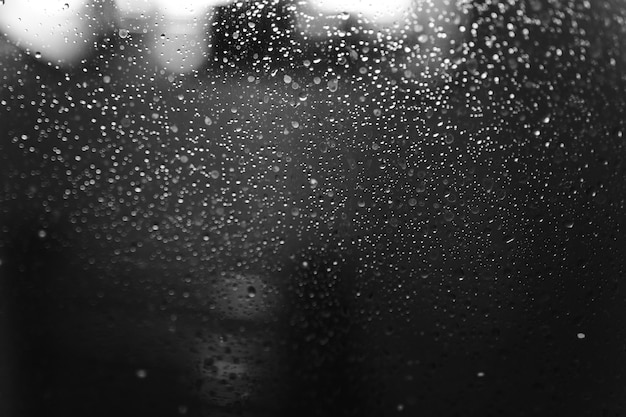 Nahaufnahme von kondensationsmustern auf glasfenster, wassertröpfchen mit lichtreflexion und -brechung, abstrakter schwarzweiss-hintergrund.