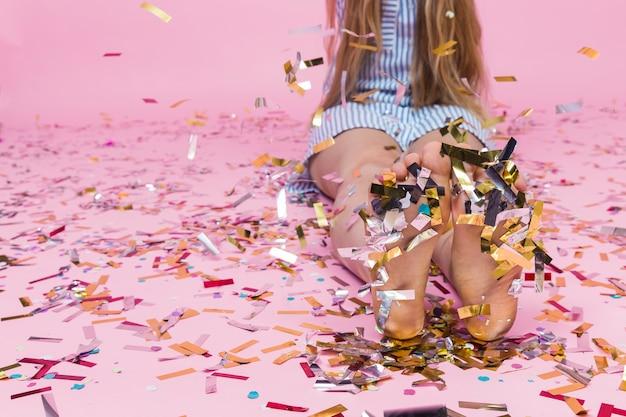 Nahaufnahme von konfetti, die über die füße der frau fallen