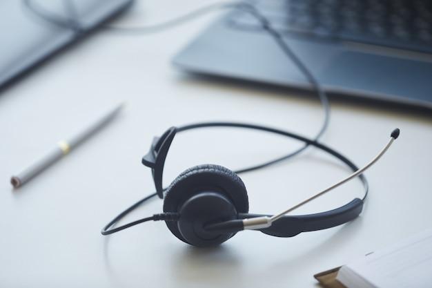 Nahaufnahme von kopfhörern, die auf dem tisch des kundendienstbetreibers im büro liegen