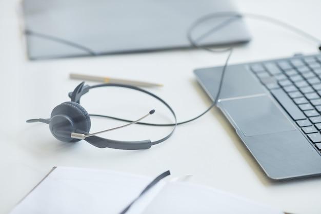 Nahaufnahme von kopfhörern mit laptop auf dem tisch der arbeitstag ist vorbei