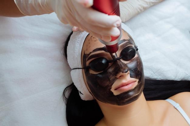 Nahaufnahme von kosmetikerinnen, die hardware-kohlenstoff-peeling durch junge hübsche kundenfrau in sicheren...