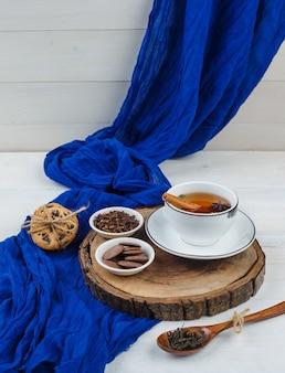 Nahaufnahme von kräutertee, nelken und pfannkuchen auf holzbrett mit keksen
