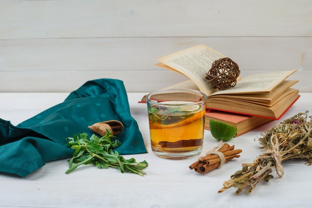 Nahaufnahme von kräutertee und blumen mit büchern, zitrone, gewürzen und grünem schal