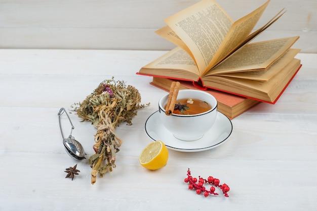 Nahaufnahme von kräutertee und blumen mit zitrone, teesieb und gewürzen