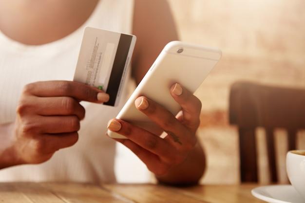 Nahaufnahme von kreditkarte und smartphone in den händen der frau