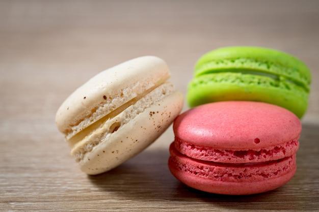 Nahaufnahme von kuchenmakronen oder makronen auf holzhintergrund mit kopierraum, süßes dessert