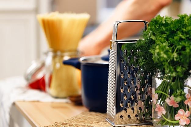 Nahaufnahme von küchentisch mit reibe kochtopf und rohe spaghetti