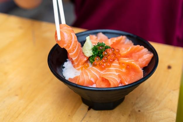 Nahaufnahme von lachs don, frischem sashimi, rohem lachs, lachsrogen, wasabi auf holztisch.