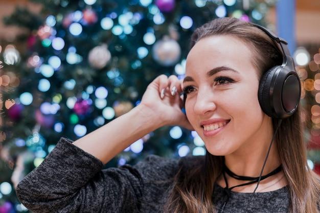Nahaufnahme von lächelnden weiblichen tragenden kopfhörern nahe weihnachtsbaum
