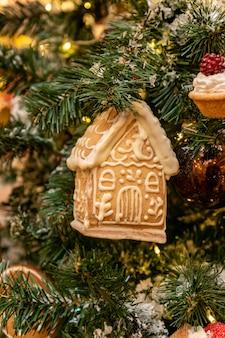 Nahaufnahme von lebkuchen-spielzeughaus sa christms-baumdekoration, die an einem tannenzweig-symbol für neue...