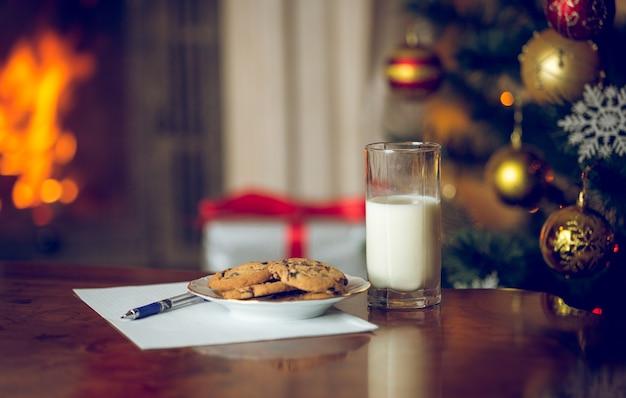 Nahaufnahme von leckereien und brief an den weihnachtsmann auf holztisch neben weihnachtsbaum