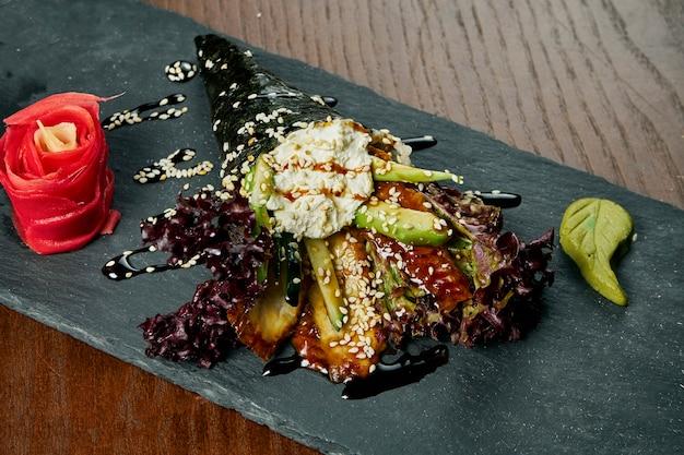 Nahaufnahme von leckerem handröllchensushi in mamenori mit aal und tobico-kaviar, serviert auf dunklem steinteller mit sojasauce und ingwer. temaki, japanische küche. gesundes essen
