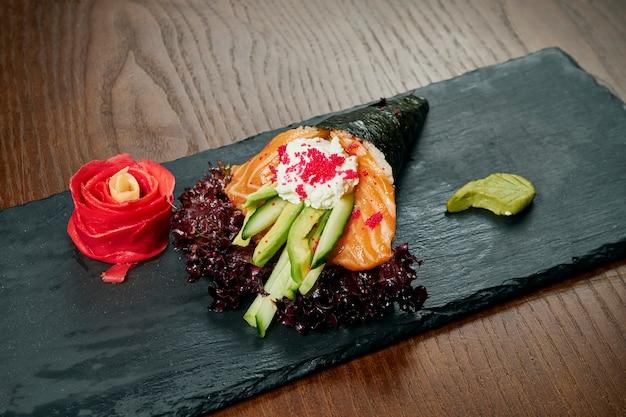 Nahaufnahme von leckerem handröllchensushi in mamenori mit lachs und tobico-kaviar, serviert auf dunklem steinteller mit sojasauce und ingwer. temaki, japanische küche. gesundes essen