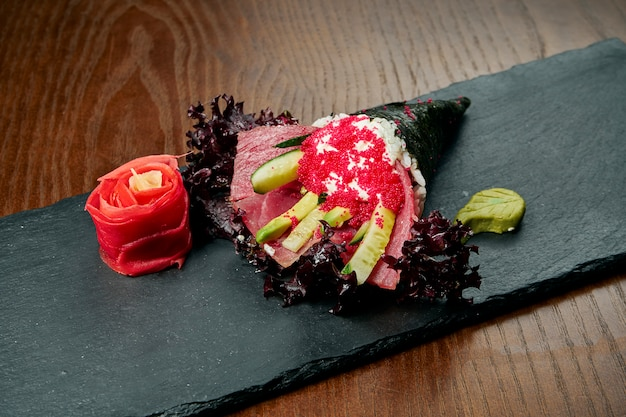 Nahaufnahme von leckerem handröllchensushi in mamenori mit thunfisch und tobico-kaviar, serviert auf dunklem steinteller mit sojasauce und ingwer. temaki, japanische küche. gesundes essen