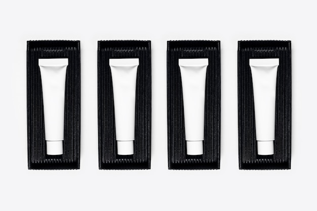 Nahaufnahme von leeren kosmetikschlauchflaschen, verpackung in blackbox auf weißer oberfläche