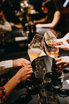 Nahaufnahme von leuten mit gläsern champagner an einem restaurant.