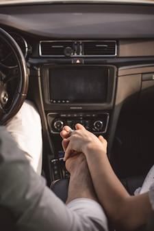 Nahaufnahme von liebespaaren, die mit dem auto reisen und die hand im sommerhintergrund halten, konzentrieren sich auf die hände