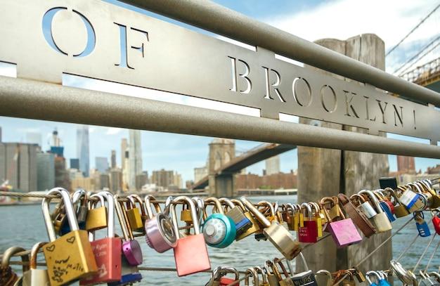 Nahaufnahme von liebesschlössern im zaun mit brooklyn bridge von new york city im hintergrund