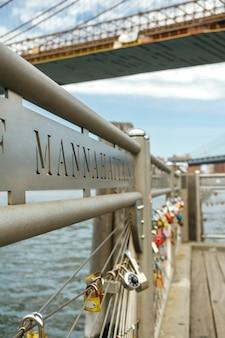 Nahaufnahme von liebesschlössern im zaun mit east river von new york city im hintergrund