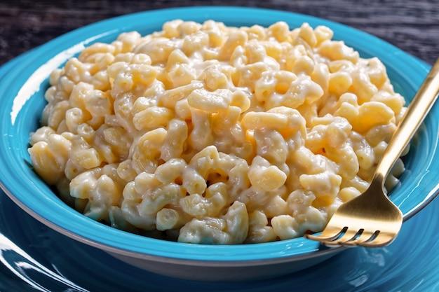 Nahaufnahme von mac und käse in einer blauen schüssel mit goldener gabel und serviette auf einem holztisch, horizontale ansicht von oben