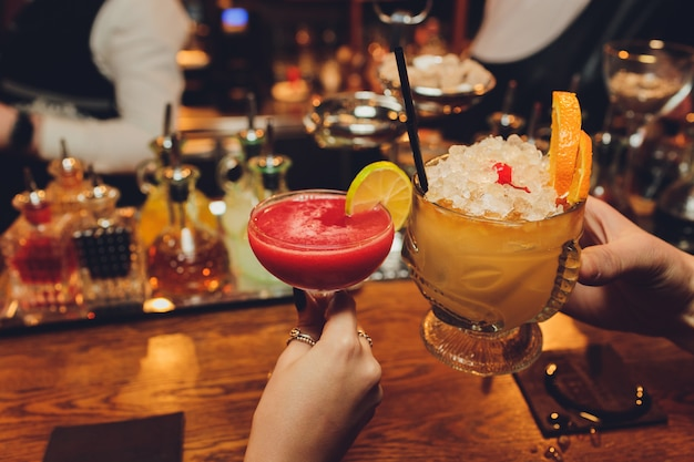 Nahaufnahme von mädchen, die cocktails im nachtclub trinken. mädchen, die gute zeit haben, jubeln und kalte cocktails trinken, freundschaft in der bar zusammen genießen, nahaufnahme auf händen.