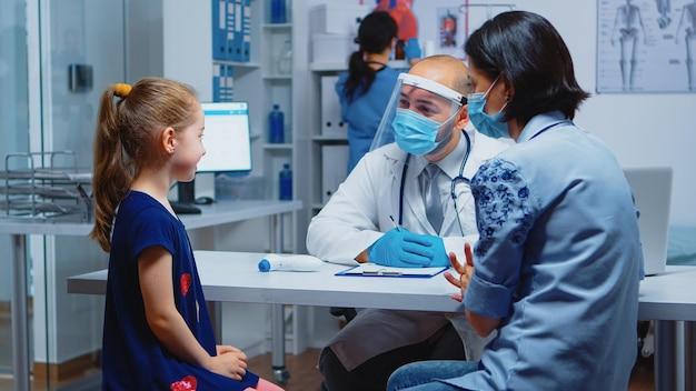 Nahaufnahme von mädchenporträt im gespräch mit arzt über ihre symptome. kinderarzt, facharzt für medizin mit maske, die während covid-19 im krankenhauskabinett beratung im gesundheitswesen anbietet
