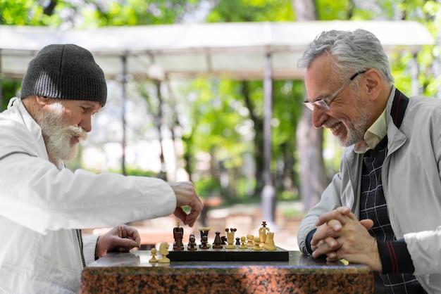 Nahaufnahme von männern, die draußen zusammen schach spielen