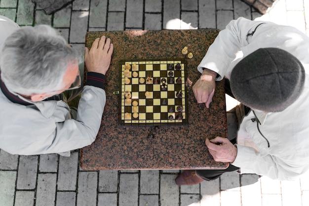 Nahaufnahme von männern, die zusammen schach spielen, ansicht von oben