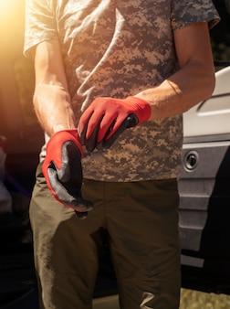 Nahaufnahme von männlichen händen des automechanikers, die arbeitshandschuhe anziehen