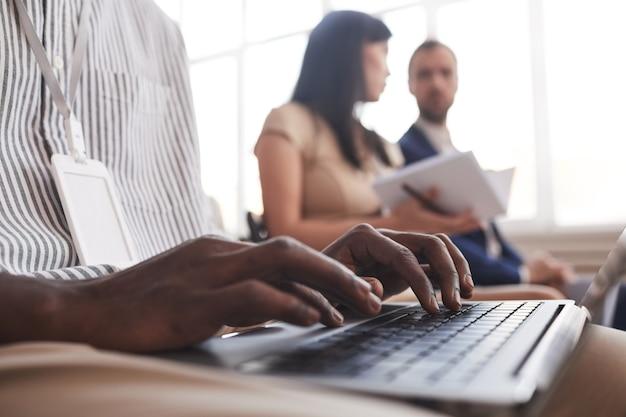 Nahaufnahme von männlichen händen, die auf der tastatur tippen, während sie auf einer geschäftskonferenz oder im seminar im publikum sitzen, platz kopieren
