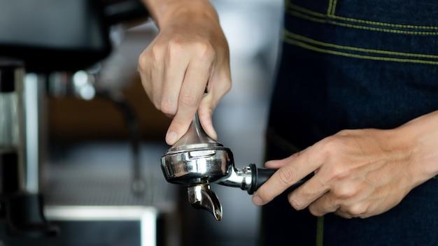 Nahaufnahme von männlichen händen, die einen metallstopfer und einen siebträger mit kaffee in einem café halten. ein mann-barista, der sich auf das pressen von gemahlenem kaffee zum brauen von espresso oder americano in einem café vorbereitet.