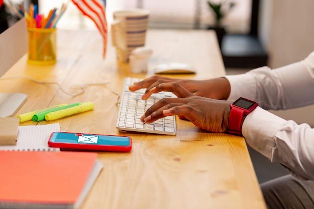 Nahaufnahme von männlichen händen, die während der texteingabe auf die tastatur drücken
