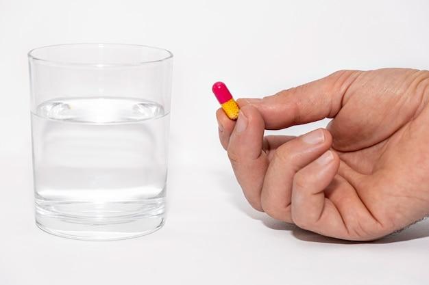 Nahaufnahme von männlichen händen halten pille vitaminpräparat mit glas wasser auf weißem hintergrund