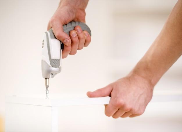 Nahaufnahme von männlichen händen mit bohrgerät.