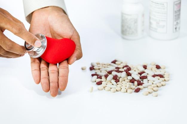 Nahaufnahme von männlichen händen mit stethoskop und rotem herzsymbol über pille auf tabelle