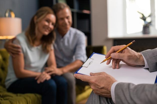 Nahaufnahme von männlichen psychotherapeutenhänden, die mit einem bleistift auf papier schreiben, während sie neben dem verheirateten paar in seinem büro sitzen
