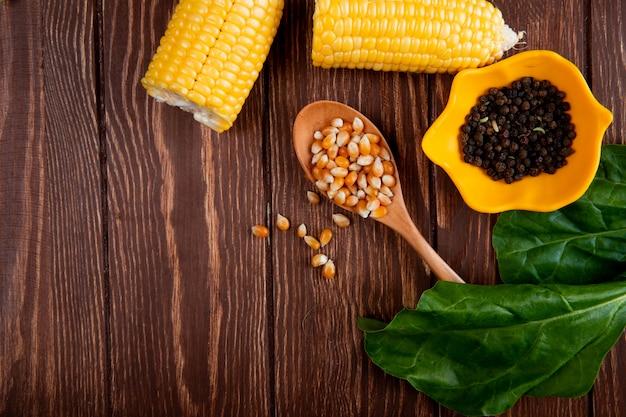 Nahaufnahme von maissamen in löffel und schwarzen pfeffersamen in schüssel mit körnern und spinat auf holztisch mit kopienraum