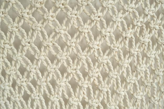 Nahaufnahme von makramee handgefertigt, dekorative platte aus leichten baumwollseilen an der wand gewebt, abstrakter texturhintergrund