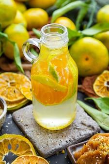 Nahaufnahme von mandarinenwasser in einer flasche auf einem tisch mit trockenen zitrusfrüchten und blättern