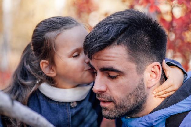 Nahaufnahme von mann und mädchen familienporträt fantastischer dunkelhaariger mann und flüsterte kleines mädchen in blauer jacke ...